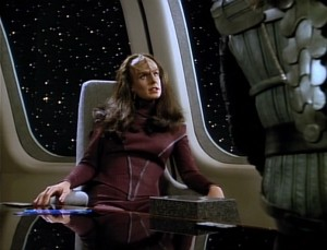 Ambassador K'Ehleyr siting in the Enterprise's observation lounge.